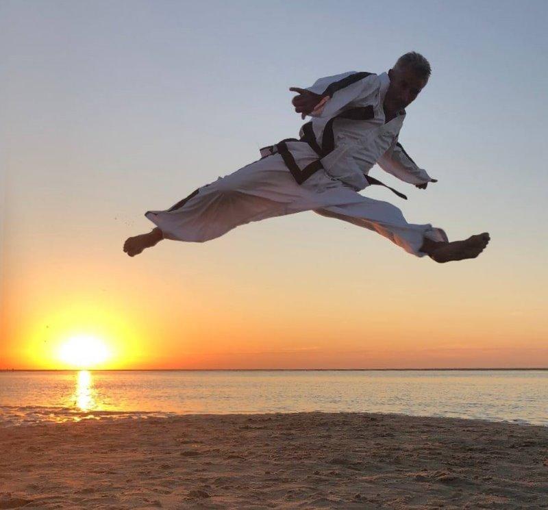 sabum Bernd Brandt maakt een gesprongen split kick aan het strand